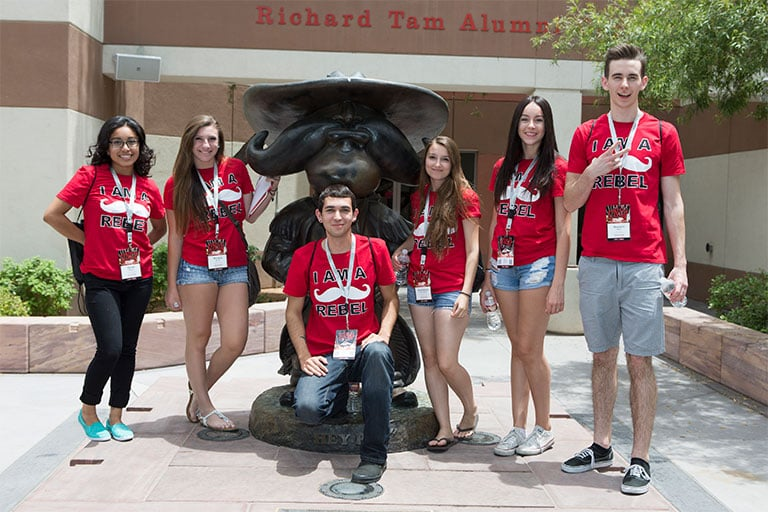 Students pose with Hey Reb! statue during Orientation.