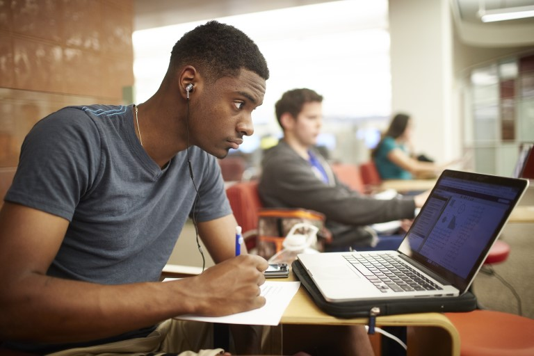 Man writing on paper while looking at laptop