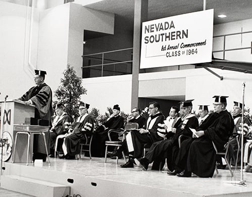 Dignitaries sitting on stage during commencement with a banner reading Nevada Southern first annual commencement, class of 1964.