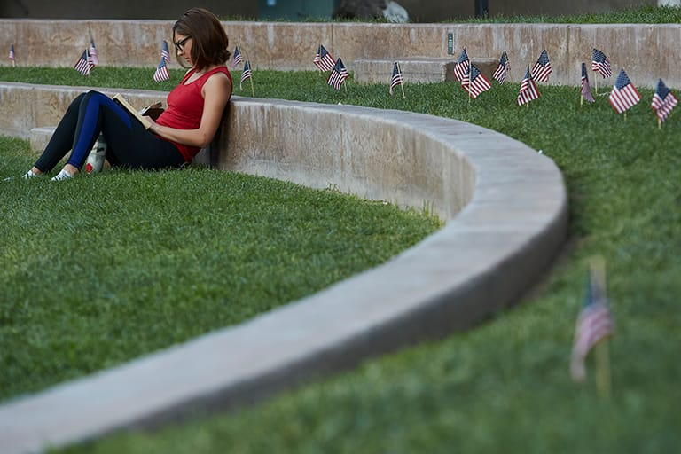 Student studying with American flags around her
