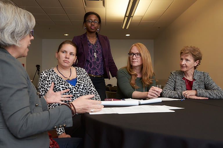 Five female faculty and staff members talking at a table.