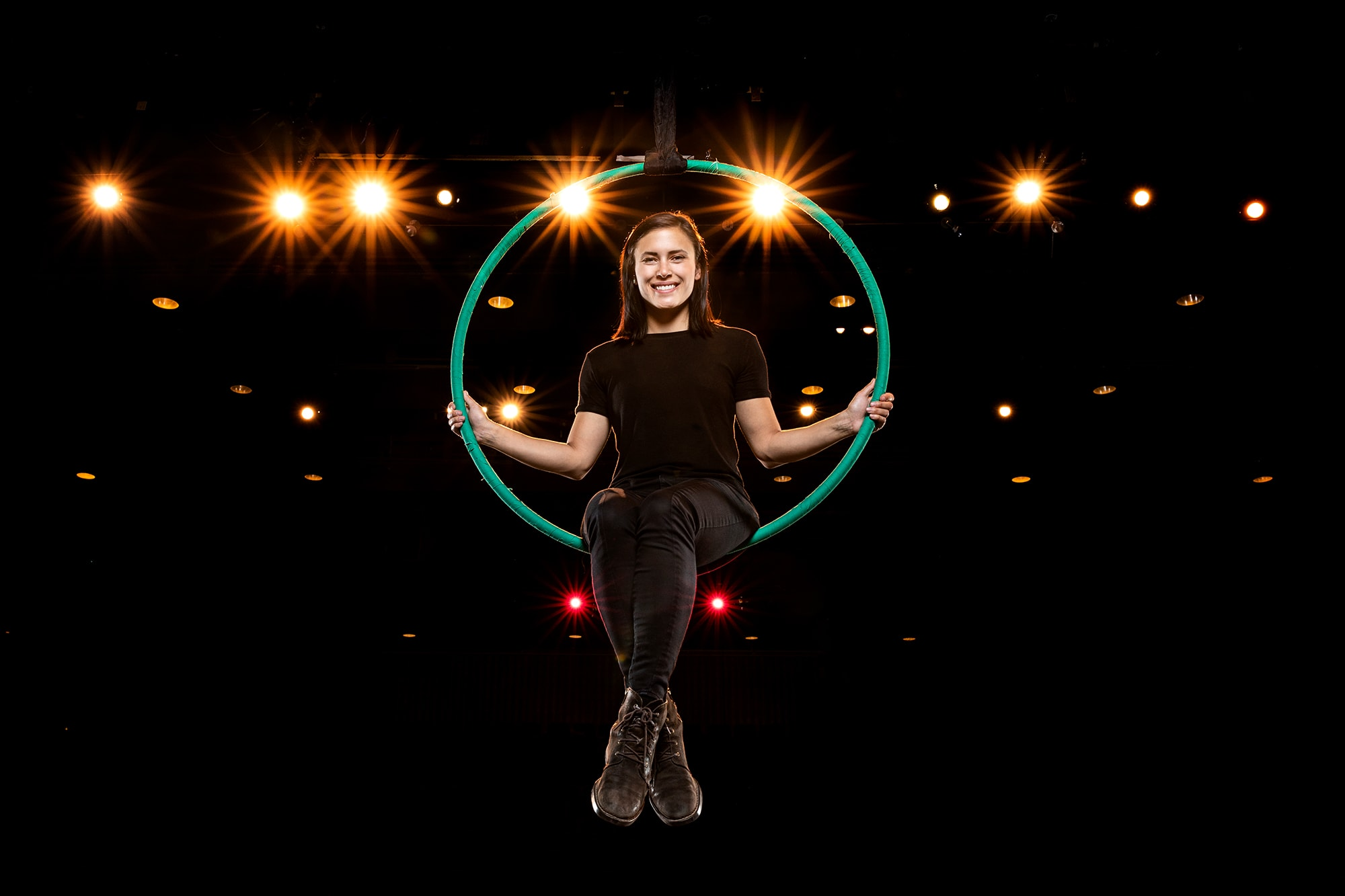 a woman sits on a hanging hoop with lights behind her
