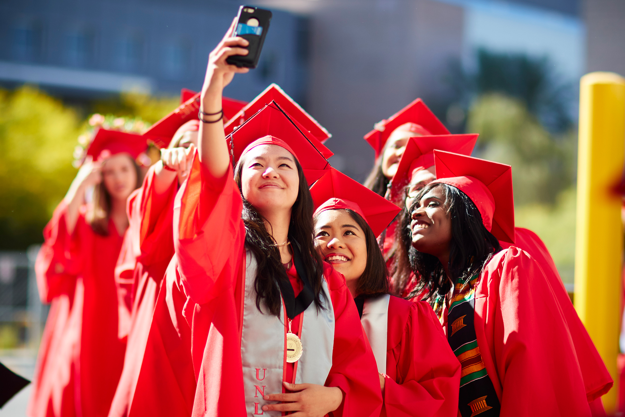 75a798d57f3 Group of people in graduation gowns taking selfie