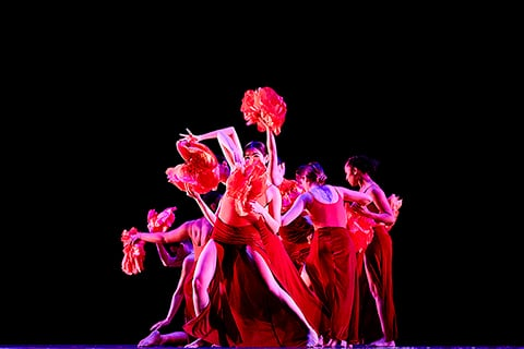 A group of dancers under red lights