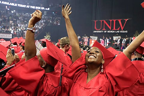 Female graduate raises her hands up in celebration during commencement