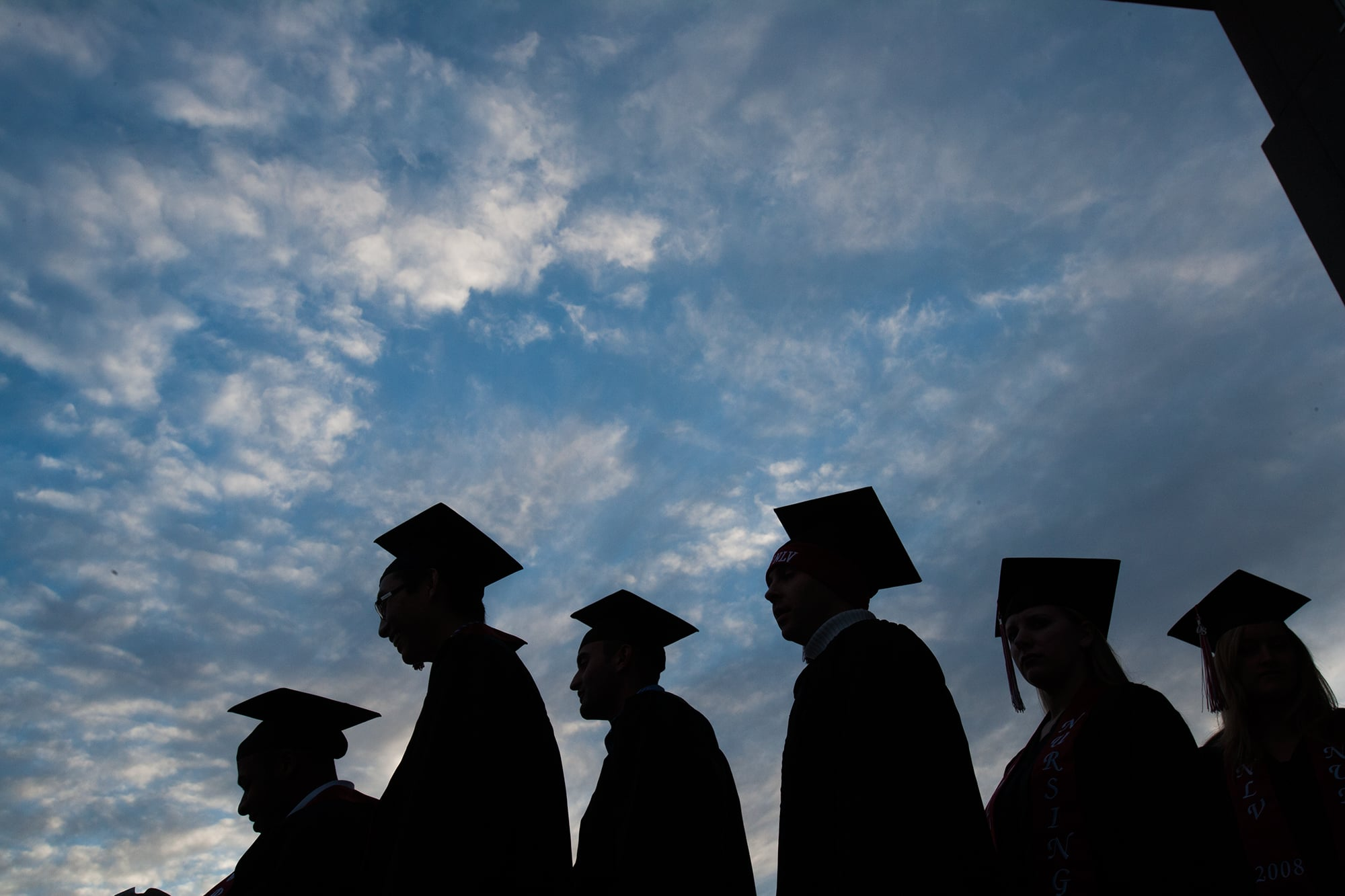silhouette of six students in cap and gown during a cloudy sunset