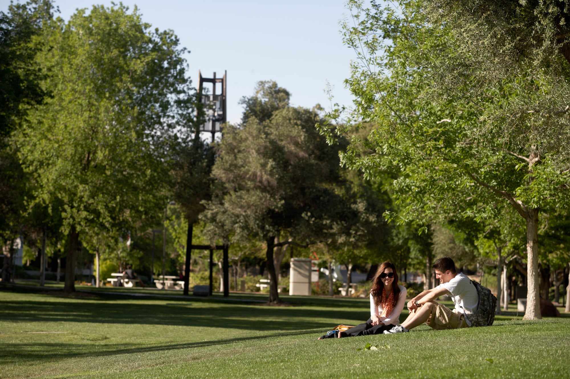 A male and female student sit together in a grassy area on the UNLV campus.