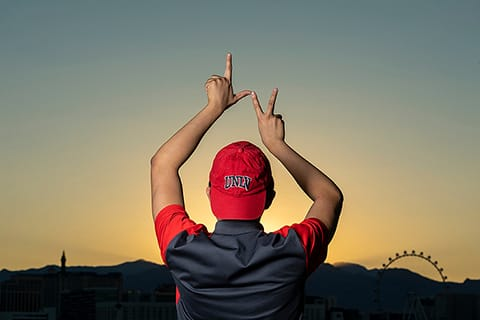 Student with U.N.L.V. cap forms hands into an L.V. sign