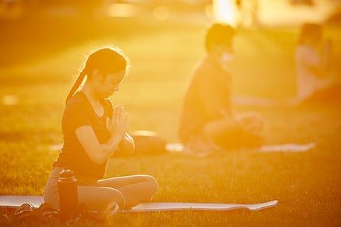 Students perform yoga outside during sunset