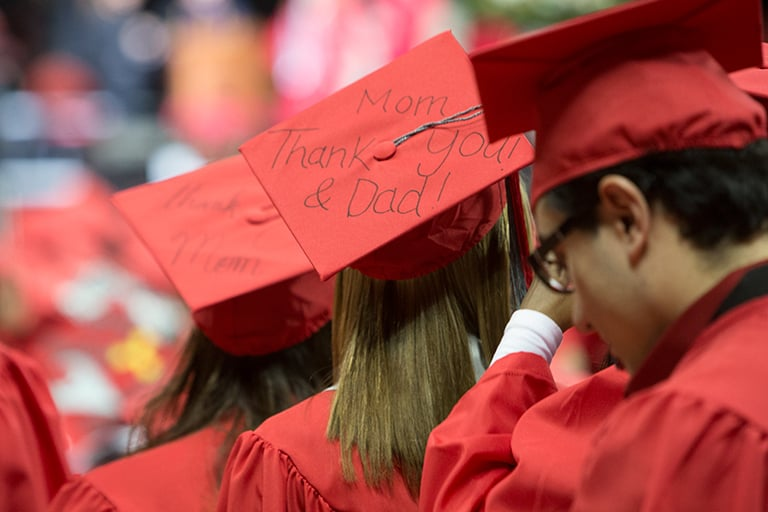 The back of students standing at commencement with Thank You Mom and Dad on the center cap.