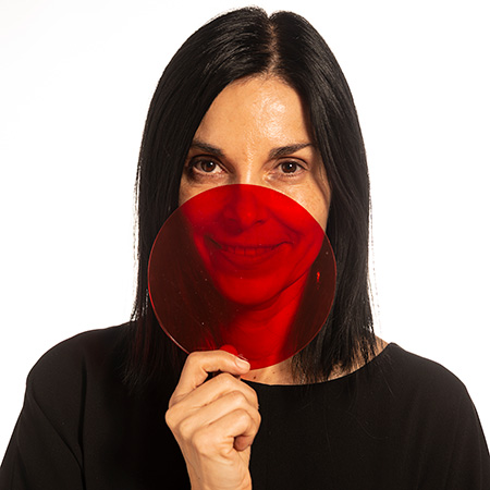A woman holding up a red circle.