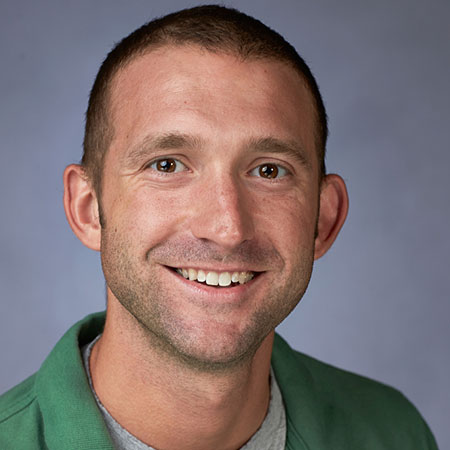 A smiling man in a green shirt.