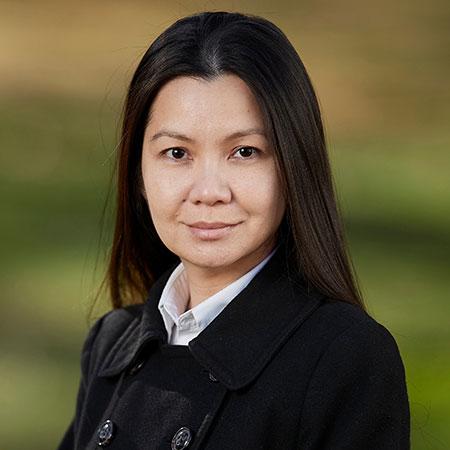 A smiling woman wearing a black jacket.