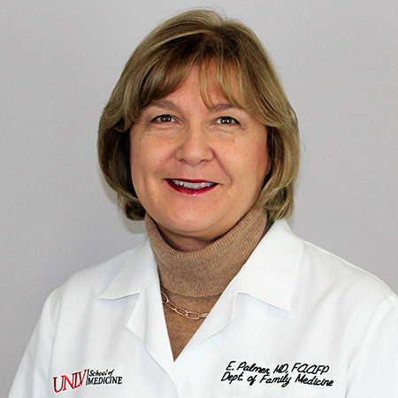 A smiling woman wearing a white lab coat