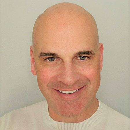 A bald man smiling.
