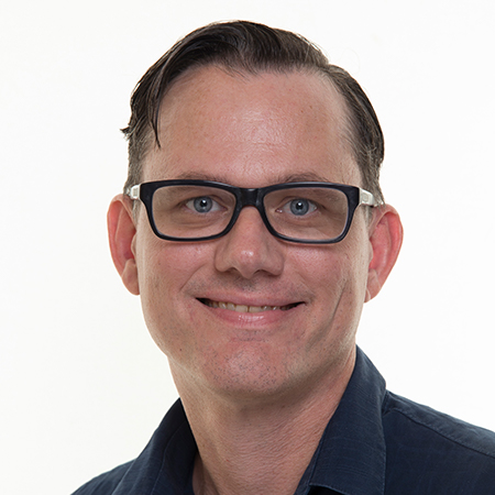 A man with glasses smiling