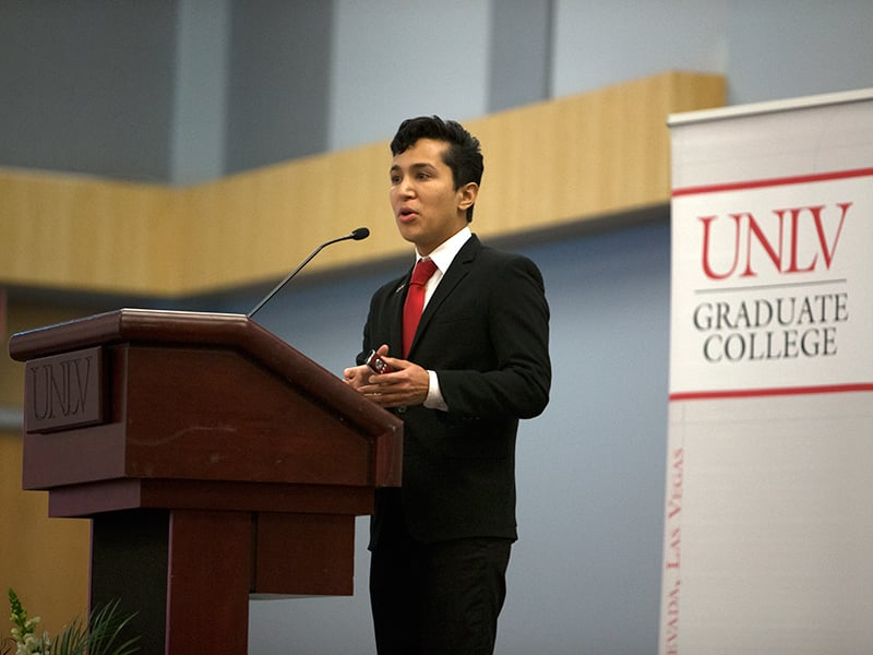 Speaker behind a UNLV podium with a Graduate College logo behind him