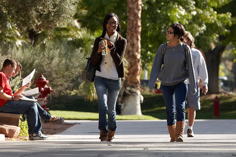 Two female students walking outside on campus