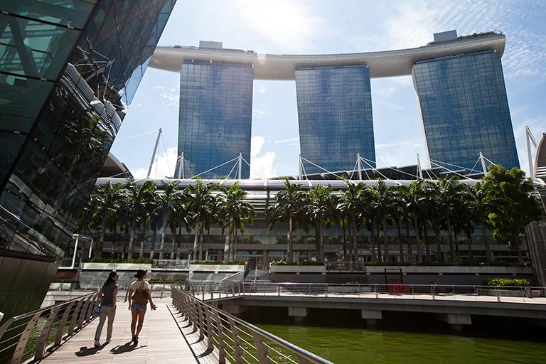 Two women walking alongside large buildings.