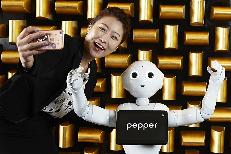 Woman taking a selfie with a robot