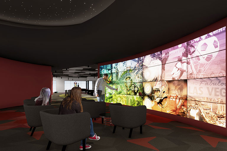 Two woman and a man looking at a massive multiscreen display with aspects of UNLV on different screens.