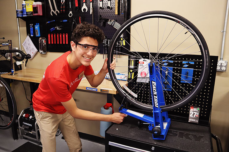 A student fixing a bicycle