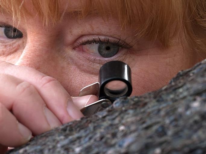 A woman examining a rock