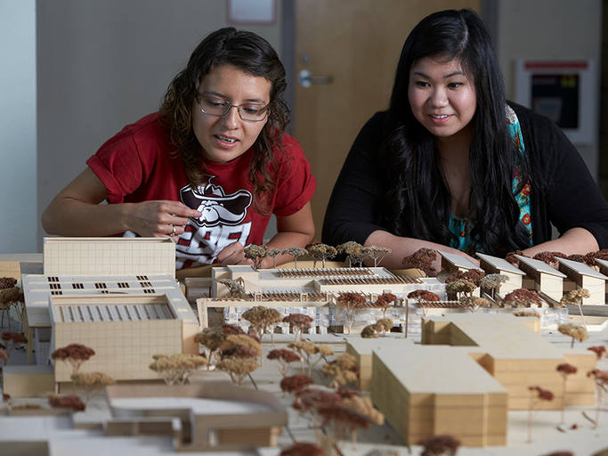 Two students looking at an architectural model