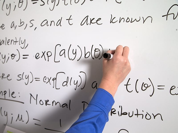 A person writing an equation on the whiteboard
