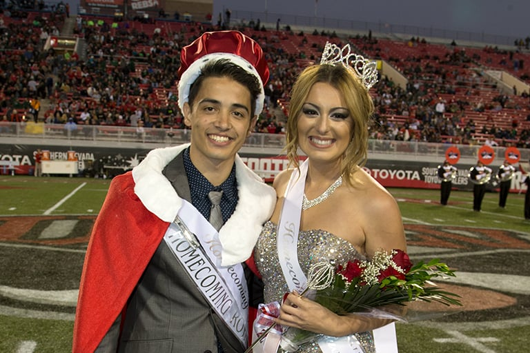 The king and queen of Homecoming standing on the football field.