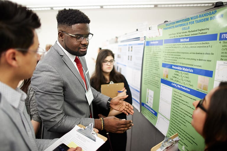 Students discussing a research poster