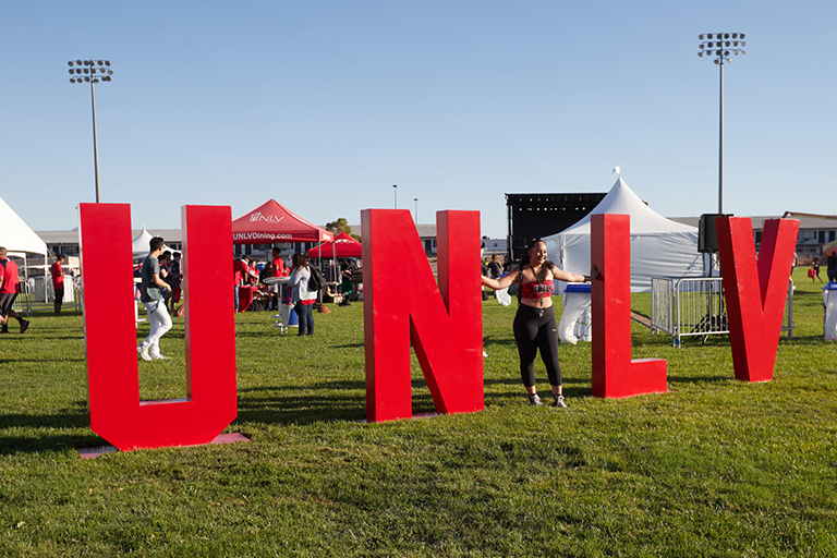 large UNLV letters with person standing next to it