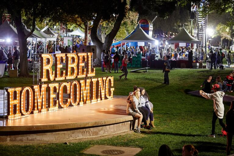 Two students taking a photo by the Rebel Homecoming sign