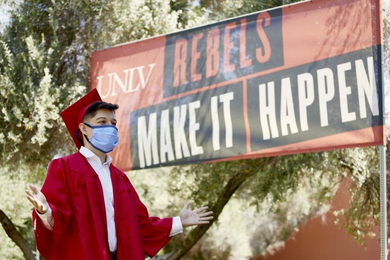 Graduate with mask in front of Rebels Make it Happen sign