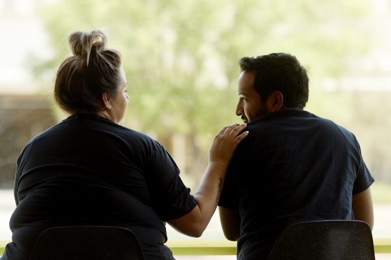 Woman and man sitting with hand on shoulder
