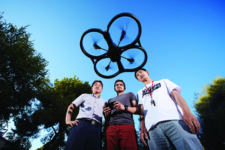 Three men flying a four-propeller drone