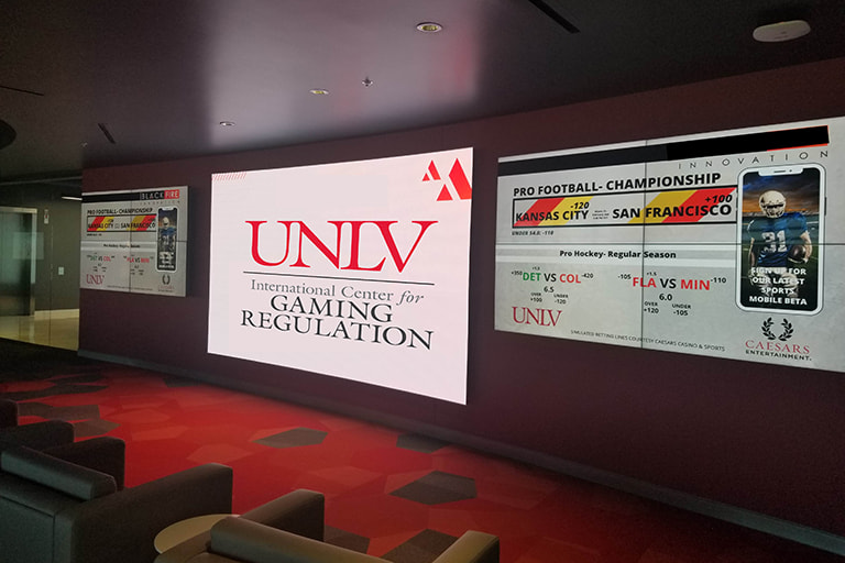 A room with the UNLV Gaming Regulation and scores of pro football championship on games on projector.