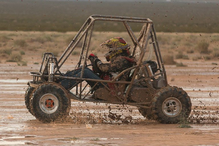 Person driving a vehicle through mud.