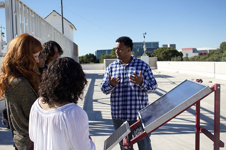 Man talking in front of solar panel.