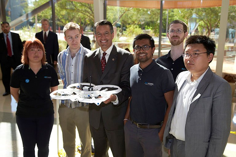 Group posing in front of a drone.