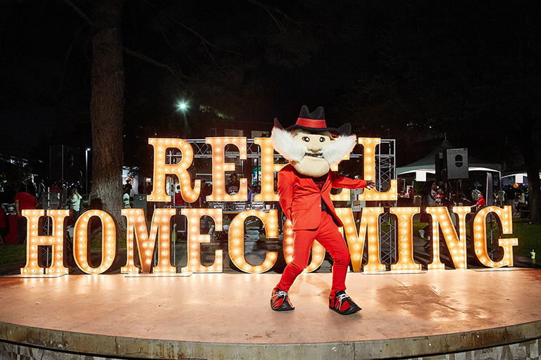 Hey Rebel mascot in front of a neon sign
