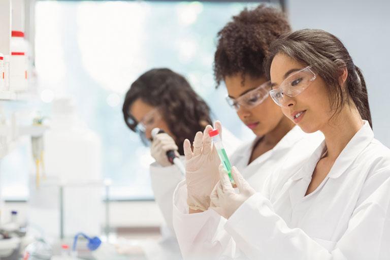 Three students doing lab work