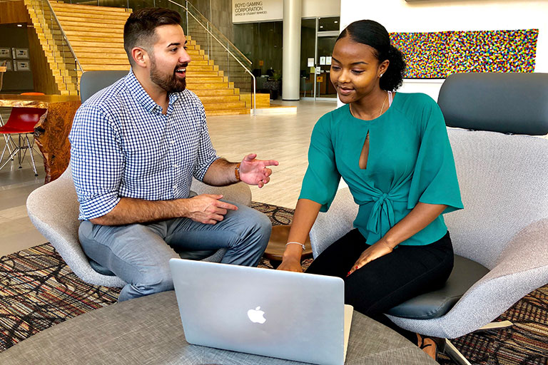 A man and a woman having a conversion while looking at a laptop