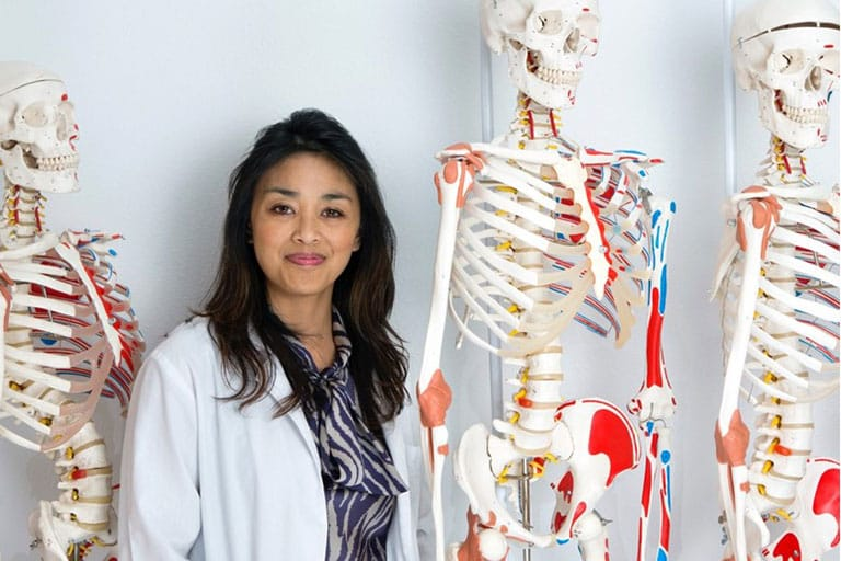 Researcher poses with skeletons