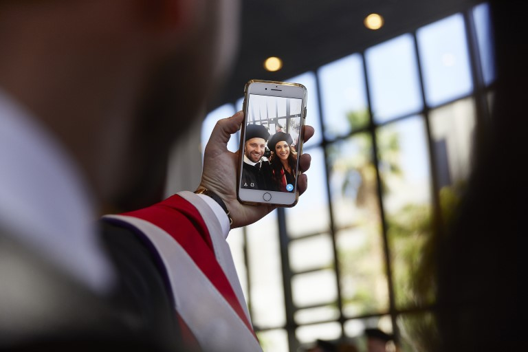 Graduate taking selfie