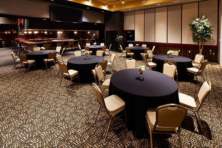 Large indoor event space with six evenly spaced round table with dark blue tablecloths and six white chairs around each table