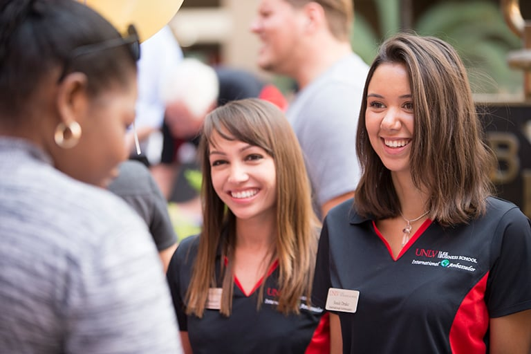 Two business majors with black polo shirts on UNLV campus.