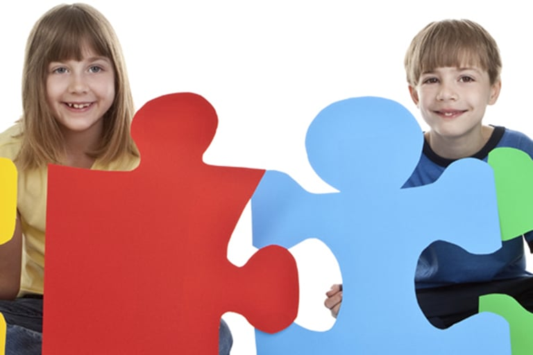 Children pose with large puzzle pieces.