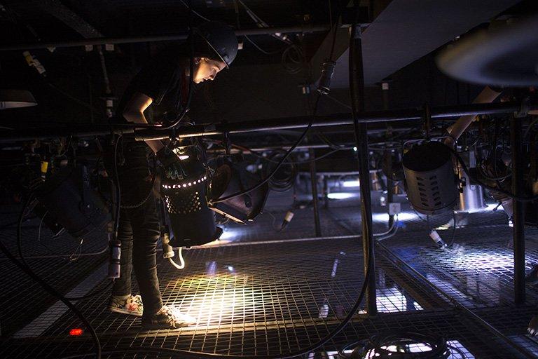 Theater tech operating lights.