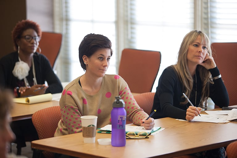 Three women sitting in two rows of tables, listening and taking notes.